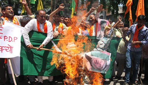 Activists of Hindu right-winged Shiv Sena burn an effigy of Kashmiri separatist leader Shabir Ahmad Shah along with a flag of Pakistan in Jammu, India, Saturday, May 30, 2015. The activists were protesting the waving of Pakistani flags in a rally organized by Shah in Srinagar on Friday. (AP Photo)